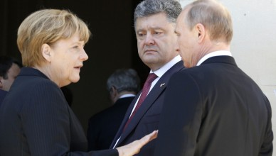 German Chancellor Angela Merkel, left, Russian President Vladimir Putin, right, and Ukrainian president-elect Petro Poroshenko, center, talk after a group photo before a luncheon as they take part in the 70th anniversary of D-Day in Benouville in Normandy, France, Friday, June 6, 2014. World leaders and veterans gathered by the beaches of Normandy on Friday to mark the 70th anniversary of World War Two's D-Day landings. (AP Photo/Regis Duvignau, Pool)