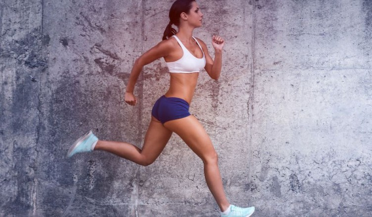 41560089 - keep on running.  full length side view of beautiful young woman in sports clothing running with a concrete wall in the background