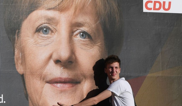 3198262 09/22/2017 A man stands by a poster featuring German Chancellor Angela Merkel, leader of the Christian Democratic Union, is seen here on a Berlin street on the eve of the German federal election. Grigoriy Sisoev/Sputnik
