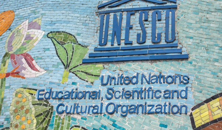 25092727 - hanoi, vietnam - circa march 2012: unesco logo on longest mosaic wall in the world. blue logo and name on colorful fresco.