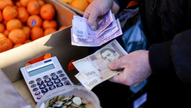 A market trader counts out hryvnia currency banknotes at a fruit stall in Kiev, Ukraine, on Monday, Feb. 3, 2014. Ukraine's opposition got a boost in its struggle to wrest power from President Viktor Yanukovych as a report said the European Union and U.S. are working on an aid package to rival assistance from Russia. Photographer: Vincent Mundy/Bloomberg
