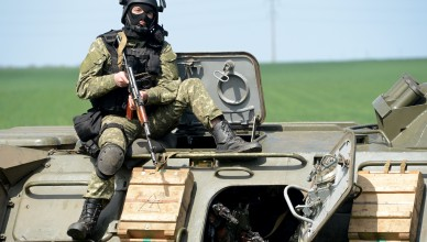 A member of the Ukrainian special forces takes position atop an armoured personnel carrier (APC) in the eastern Ukrainian city of Slavyansk on April 24, 2014. Ukraine's military launched an assault on the flashpoint rebel-held town of Slavyansk, sending in armoured vehicles and a helicopter, AFP journalists in the town reported. Several armoured personnel carriers drove past an abandoned rebel roadblock in flames to take up position at the entry to the town. AFP PHOTO/KIRILL KUDRYAVTSEV