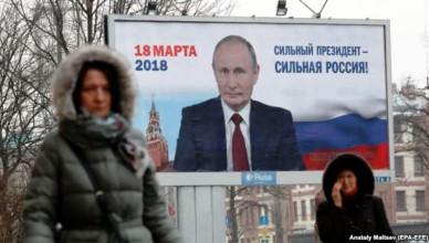 epa06433588 People walk past an election poster reading 'Strong President Strong Russia' in support of Russian President Vladimir Putin, a self-nominated candidate in the upcoming presidential election on the Moscowsky prospect in St.Petersburg, Russia, 12 January 2018. Presidential elections in Russia is scheduled for 18 March 2018.  EPA-EFE/ANATOLY MALTSEV