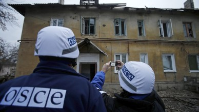 An Organization for Security and Cooperation in Europe (OSCE) investigator takes pictures of a building after it was damaged by recent shelling in the western part of Donetsk, eastern Ukraine, November 27, 2014. REUTERS/Antonio Bronic (UKRAINE  - Tags: CONFLICT CIVIL UNREST)