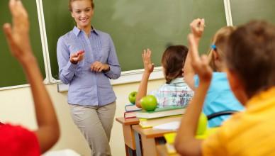 Portrait of smart teacher by blackboard looking at schoolkids in classroom