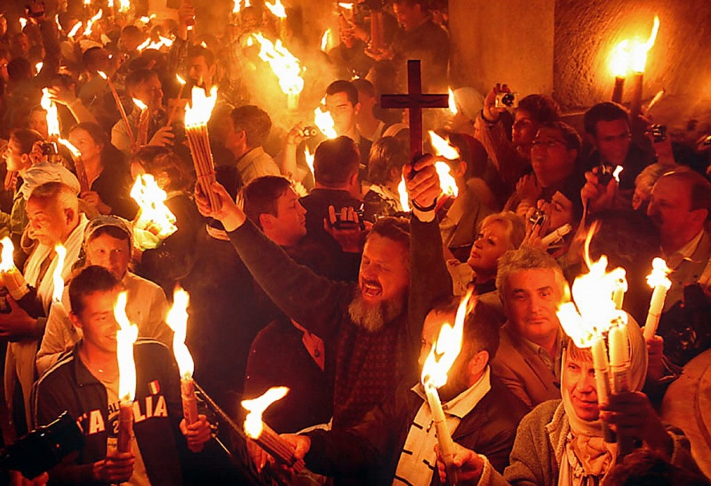 Christian Orthodox worshippers hold up candles lit from the 'Holy Fire' as thousands gather in the Church of the Holy Sepulchre in Jerusalem's old city on April 23, 2011 during the 'Holy Fire' ceremony on the eve of the Orthodox Easter. The ceremony celebrated in the same way for 11 centuries, is marked by the appearance of 'sacred fire' in the two cavities on either side of the Holy Sepulchre. The Holy Sepulchre in Jerusalem is the site of the final resting place of Jesus Christ, according to Christian tradition. AFP PHOTO/GALI TIBBON