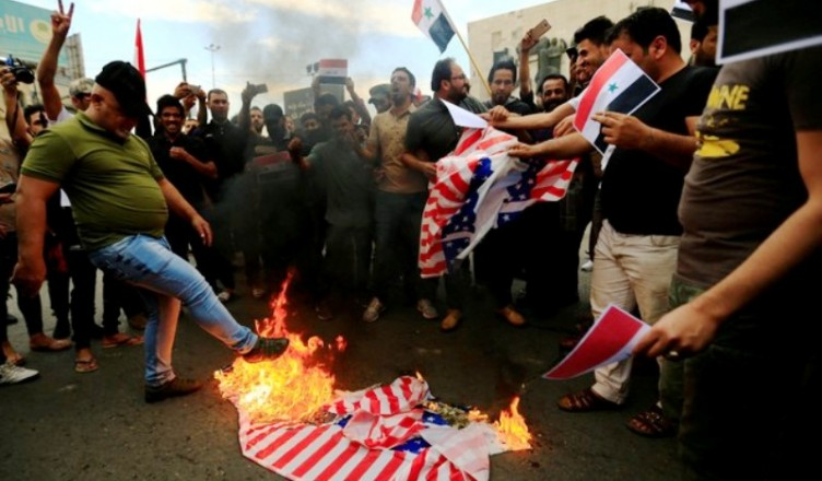 Supporters of Iraqi Shi'ite cleric Moqtada al-Sadr burn a U.S flag during a protest against western air strikes on Syria, at Tahrir Square in Baghdad, Iraq April 15, 2018. REUTERS/Thaier Al-Sudani
