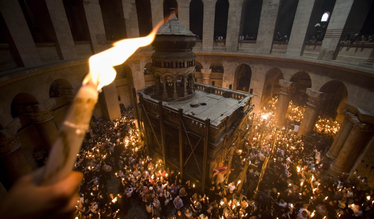 FILE - In this April 3, 2010 file photo Orthodox Christian pilgrims hold candles at the Church of the Holy Sepulcher, traditionally believed to be the site of the crucifixion of Jesus Christ, during the Holy Fire ceremony, in Jerusalem's Old City. Thousands of Christian believers will fill the medieval chambers of the Church of the Holy Sepulcher in Jerusalem on Saturday April 23, 2011 for a yearly ritual known as the Holy Fire, packed shoulder to shoulder and holding burning candles as pilgrims have done for centuries. And in 2011, as in centuries past, the church will have only one door and no fire exit.(AP Photo/Bernat Armangue, File)