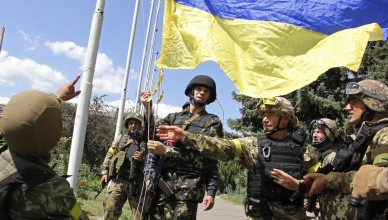 In this photo taken on Saturday, July  5, 2014, Ukrainian soldiers and Ukrainian Defense Minister Valery Heletey, third from right, raise a Ukrainian flag in downtown Slovyansk, eastern Ukraine. After Ukrainian forces' seizure of a key rebel stronghold in the east, the major cities of Donetsk and Luhansk could be the next focus of major fighting. Three bridges on roads leading to Donetsk were blown up Monday — possibly to hinder military movements, though the rebels claim it was the work of pro-Kiev saboteurs. (AP Photo/str)