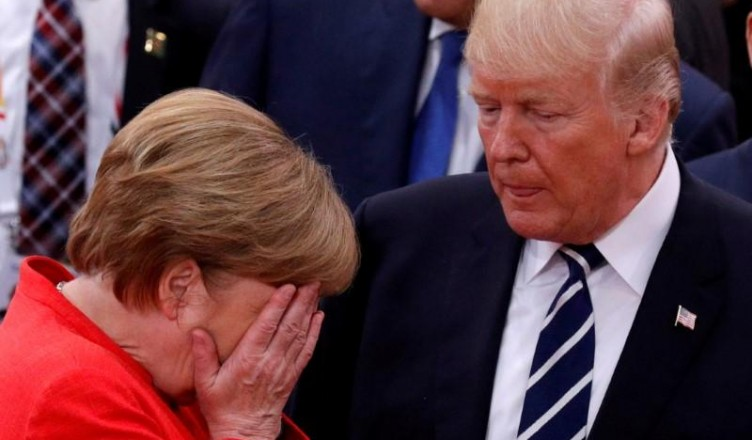 FILE PHOTO: German Chancellor Angela Merkel reacts next to U.S. President Donald Trump during the G20 leaders summit in Hamburg, Germany July 7, 2017. REUTERS/Philippe Wojazer/File Photo