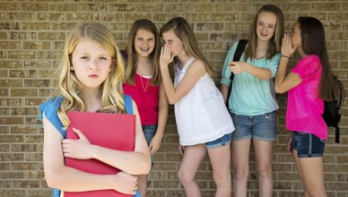 Pre-teen girl being bullied by a group of mean girls.