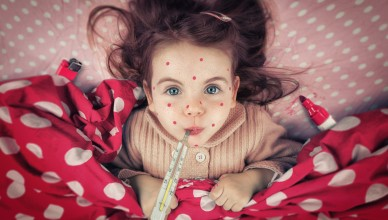 Little girl lying in bed. She obviously painted her self little red dots to pretend having measles. And she also used a lighter to bring up the measured fever up to 40 degress on the thermometer.
