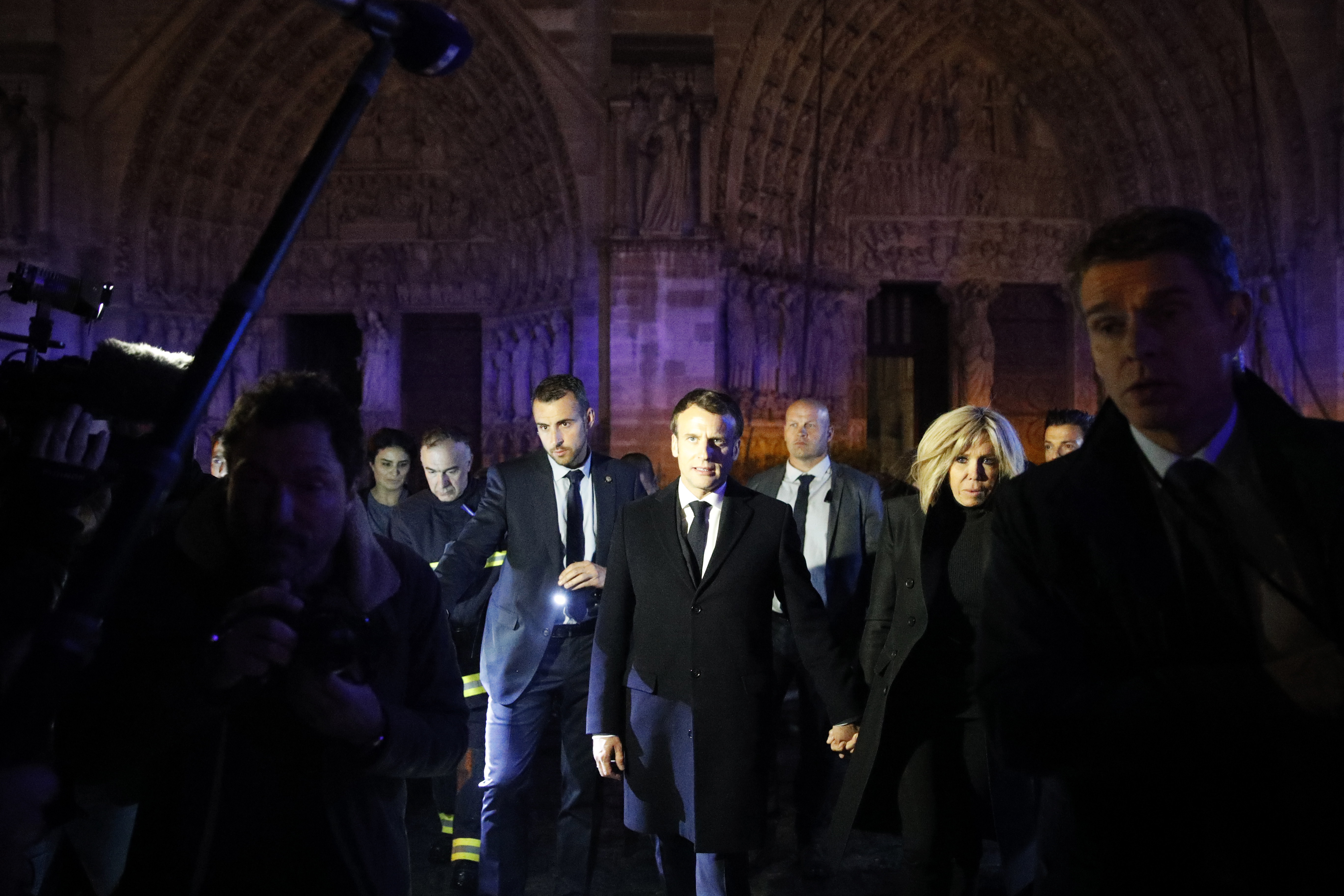 epa07509135 French President Emmanuel Macron (C) and his wife Brigitte Macron (R) pay a visit to firemen fighting against a fire burning the roof of the Notre-Dame cathedral in Paris, France, 15 April 2019. A fire started in the late afternoon in one of the most visited monuments of the French capital.  EPA-EFE/YOAN VALAT
