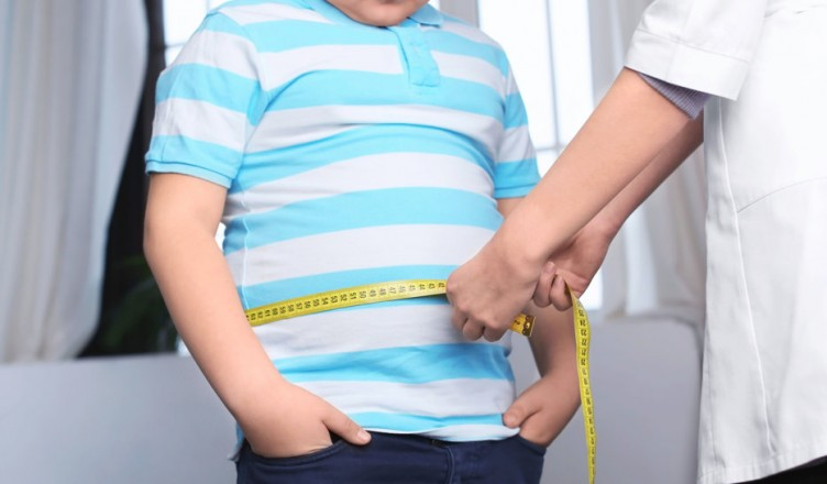 Doctor measuring overweight boy in clinic