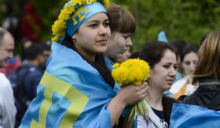 Crimean Tatars, with Crimean Tatars blue flags on, take part in climbing the Chatyr-Dag mountains to commemorate the 71st anniversary of Soviet dictator Stalin's mass deportation of Crimean Tatars, near Alushta, Crimea, Saturday, May 16, 2015. Young Tatars with the Crimean Tatars blue flags made the ascent of the Chatyr-Dag mounts massif  to honor the victims of the 1944 deportation of Crimean Tatars.  (AP Photo/Anton Volk)