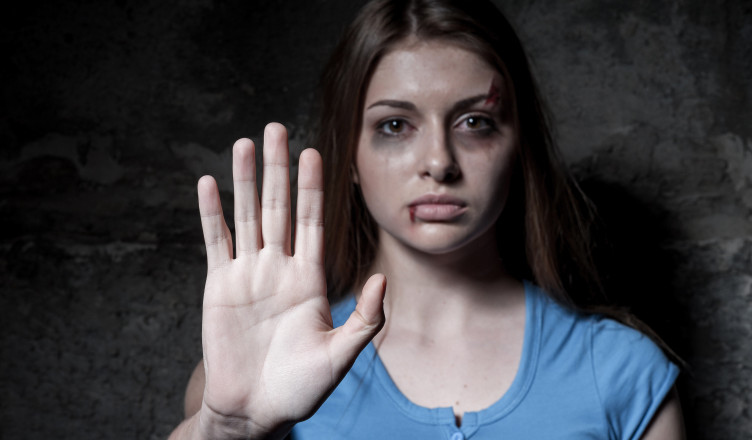Stop hurting woman! Young beaten up woman looking at camera and stretching out hand while standing against dark wall