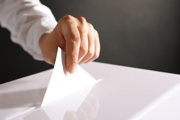 Woman putting her vote into ballot box on black background, closeup