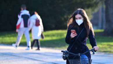 "A women wearing a protective face mask rides her bike as she looks at her smartphone in the interior courtyard of the Sforza castle in the center of Milan on January 13, 2021. - Italy's health minister announced on January 13, 2021 a partial reopening of museums, while most other coronavirus restrictions were due to be extended, measures that would apply only to less-infected ""yellow"" regions, while ""respecting all social distancing measures"". Italy, which has recorded nearly 80,000 deaths from the pandemic, has had colour-coded regional virus restrictions since November, when all the museums were shut. (Photo by Miguel MEDINA / AFP)"