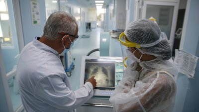 Dr. Shemsedin Dreshaj, left, head of the ICU unit looks at the X-Ray of the lungs of a patient with COVID-19 in the Clinic for Infectious Diseases in Pristina, Kosovo, Monday, Sept. 21, 2020. (AP Photo/Visar Kryeziu)