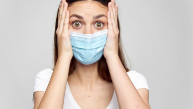 surprised-woman-in-medical-mask-touching-face-with-hands_163305-32091